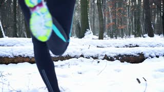 Jogger running in the forest at winter, steady, slow motion shot at 240fps