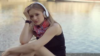Lonely girl looking very sad while listening music next to the water