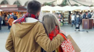 Lovely couple cuddling ath the christmas market in the town, steadycam shot