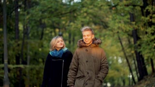 Lovely couple walking in the park and smiling to the camera