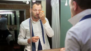 man applying an eye cream and standing before the mirror