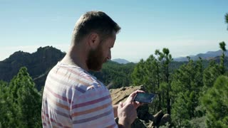 Man browsing internet on smartphone in the mountains