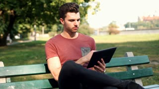 Man browsing internet on tablet and smiling to the camera in the park