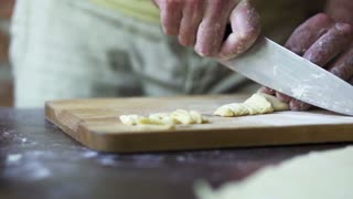man cutting dough with a knife, slow motion at 240 fps