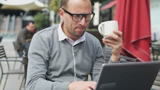 Man drinking coffee and using laptop in street cafe, steadycam shot