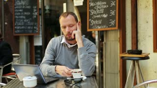 man drinking coffee outside the cafe