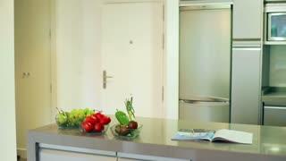 Man drinking milk in the kitchen after jogging, steadycam shot