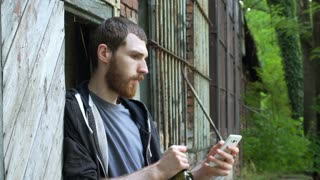 Man drinking wine and using smartphone while standing next to the abandoned buil