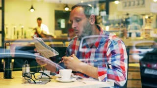 Man eating toast and reading newspaper in the cafe, steadycam shot