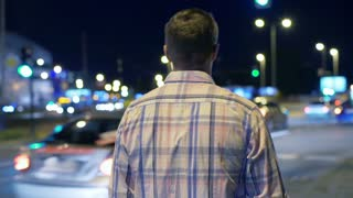 Man having a walk at night in the city, steadycam shot