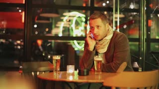 Man having an argue while talking on cellphone in pub, steadycam shot