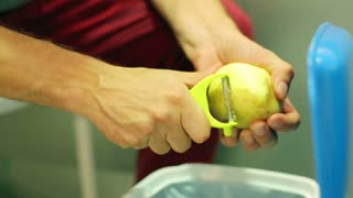 Man holding and peeling potato by using peeler