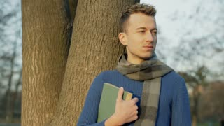 Man holding book and doing serios look to the camera in the park, steadycam shot
