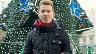 Man holding presents while standing next to the christmas tree and smiling, stea