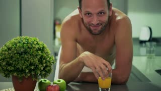 Man in the towel looking to the camera and drinking orange juice