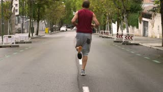 Man jogging alone on the road, slow motion shot, steadycam shot