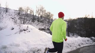 Man jogging and looking back to the camera, steady, slow motion shot at 240fps