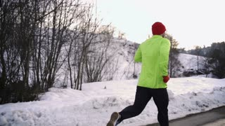 Man jogging and looking back to the camera, steady, slow motion shot