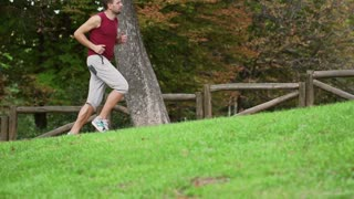 Man jogging and woman stretching in the park, slow motion shot