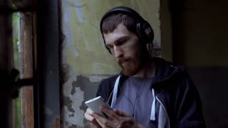 Man listening music and looking morose while standing in the abandoned building,