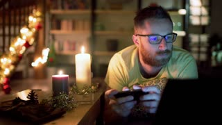 Man looking unhappy and texting on smartphone in his christmassy house