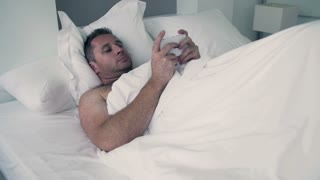 Man lying in bed under white quilt and typing message on cellphone