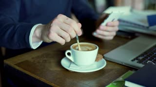 Man mixing coffee in the cafe and browsing internet on smartphone