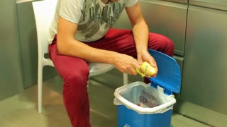 Man peeling potatio to the dustbin in the kitchen