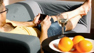 Man playing game on smartphone while lying on the sofa
