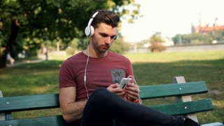 Man plays music on smartphone and listening while sitting in the park