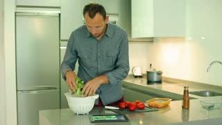 Man preparing salad using recipe on the internet and cutting tomato