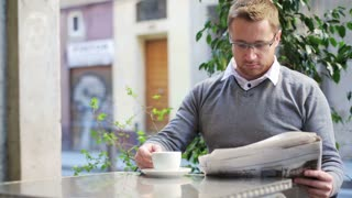 Man reading newspaper and drinking coffee.