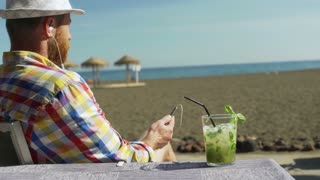Man relaxing on the beach and listening music on earphones, steadycam shot
