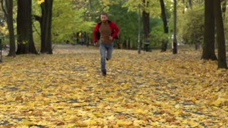 Man running in the autumnal park, slow motion shot