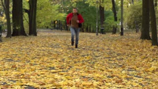 Man running in the autumnal park, steadycam shot, slow motion shot at 240fps