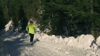 Man running in the forest at winter, steadycam shot, slow motion shot at 240fps
