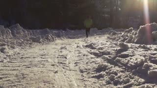 Man running on the snowy road, steadycam shot, slow motion shot