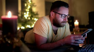 Man sitting at home and typing message on smartphone