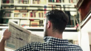 Man sitting back and reading newspaper downstairs