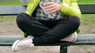 Man sitting cross-legged on the bench and using smartphone
