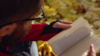 Man sitting in the park and reading book, slow motion shot