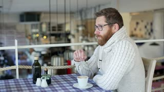Man sitting in the restaurant and mixing coffee in the cup