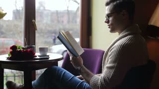 Man sitting in the restaurant and reading interesting book