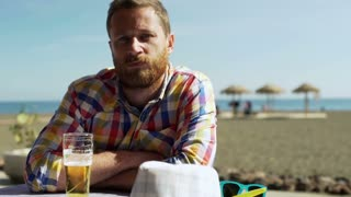 Man sitting in the restaurant on the beach and smiling to the camera