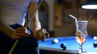 Man sitting on billiard's table and playing with ball