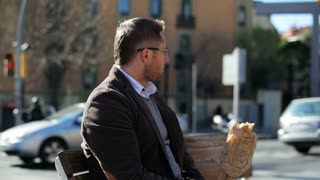 Man sitting on street bench and eating baguette, steadycam shot.