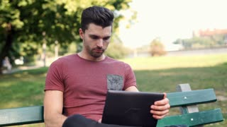 Man sitting on the bench in the park and using laptop