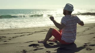 Man sitting on the sandy beach and relaxing, steadycam shot