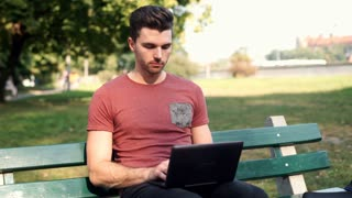 Man smiling to the camera while using laptop in the park