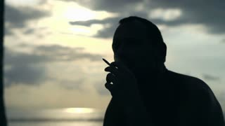 Man smoking cigarette in the evening at the seaside, slow motion shot at 240fps